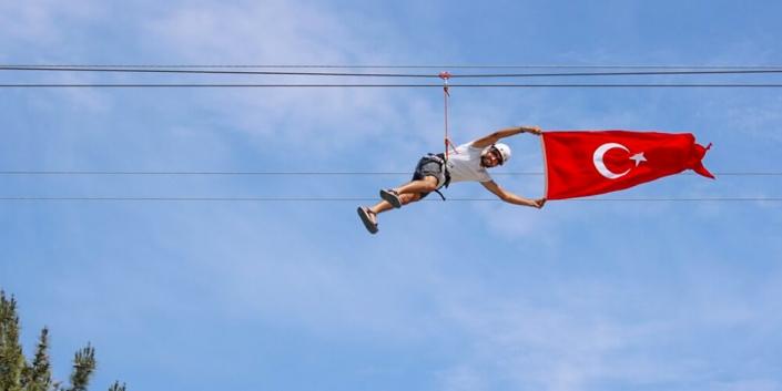 Macera parkında yer alan zipline kullanan mutlu kullanıcılar